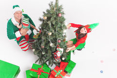 Happy family decorating Christmas tree, dressed in elf costumes Royalty Free Stock Photos