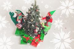 Happy family decorating Christmas tree, dressed in elf costumes. Happy family decorating Christmas tree, dressed in elf and Santa helper costumes. White royalty free stock photography