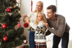 Happy family decorating christmas tree at home. Happy caucasian family decorating christmas tree at home with toys Stock Photography