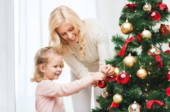 Happy family decorating christmas tree at home. Family, x-mas, winter holidays and people concept - happy mother and little daughter decorating christmas tree at royalty free stock photo