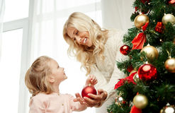 Happy family decorating christmas tree at home. Family, x-mas, winter holidays and people concept - happy mother and little daughter decorating christmas tree at Stock Images