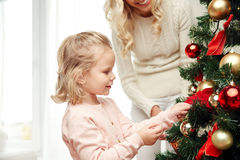 Happy family decorating christmas tree at home Royalty Free Stock Image