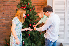 Happy family decorating Christmas tree in the room.  Stock Photography