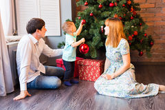 Happy family decorating Christmas tree in the room.  Royalty Free Stock Images