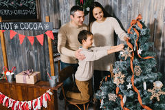 Happy Family Decorating Christmas Tree together. Father, Mother And Son Royalty Free Stock Photos