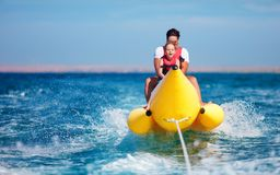Happy family, delighted father and son having fun, riding on banana boat during summer vacation Royalty Free Stock Photography