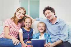 Happy family with digital tablet sitting on sofa Stock Photos