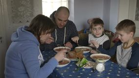 Happy family dines at the table. Traditional Ukrainian borsch dish. stock footage