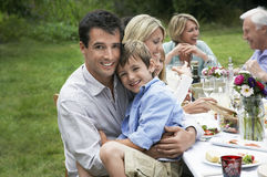 Happy Family Dining At Table In Garden Stock Image
