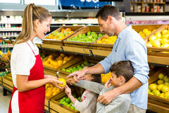Happy family discussing with worker. In grocery store Royalty Free Stock Image