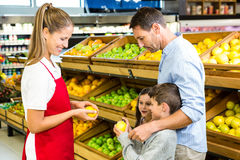 Happy family discussing with worker. In grocery store Royalty Free Stock Photo