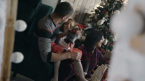 A happy family is displayed in a mirror in a room with a fireplace next to the Christmas tree. The young family gladly stock video