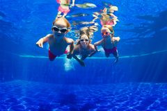 Happy family dive underwater in swimming pool. Happy family - mother, baby son, daughter in goggles swim, dive in pool with fun - jump deep down underwater royalty free stock image