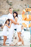Happy family with dog on berth in summer. Happy young family in white clothing have fun and play with beautiful dog at vacations  on berth in summer Royalty Free Stock Photo