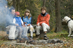 Happy family with dog near campfire Royalty Free Stock Photo