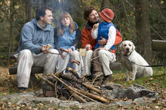 Happy family with dog near campfire Royalty Free Stock Photos