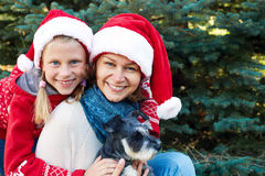 Happy family with dog near a Christmas tree on the street Royalty Free Stock Images