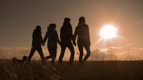 Happy family and dog silhouette walking at sunset teamwork. group of people friends walking holding hands slow motion