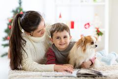 Happy family and the dog spending together Christmas time at home near the Christmas tree. New year concept. Portrait of a happy family and the dog spending royalty free stock photography