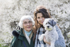 Happy family with a dog in a spring park Royalty Free Stock Photo