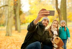 Happy family with dog taking selfie in autumn park. Family, pets and people concept - happy mother, father and little daughter with beagle dog taking selfie by royalty free stock photo
