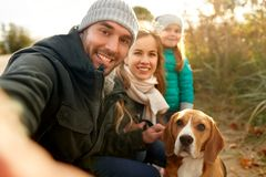 Happy family with dog taking selfie in autumn. Family, pets and people concept - happy mother, father and little daughter with beagle dog taking selfie outdoors royalty free stock image