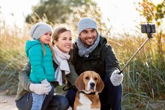 Happy family with dog taking selfie in autumn. Family, pets and people concept - happy mother, father and little daughter with beagle dog taking picture by stock photos