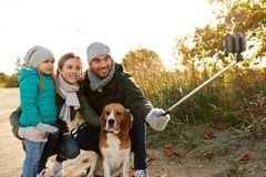 Happy family with dog taking selfie in autumn. Family, pets and people concept - happy mother, father and little daughter with beagle dog taking picture by royalty free stock images