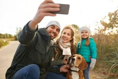 Happy family with dog taking selfie in autumn. Family, pets and people concept - happy mother, father and little daughter with beagle dog taking selfie by royalty free stock photo