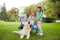 Happy family with dog taking selfie by smartphone Stock Photography