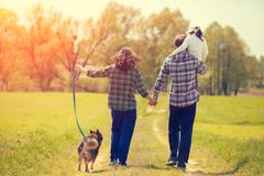 Happy family with dog walking on the rural road Royalty Free Stock Photography