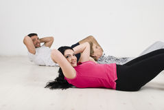 Happy family doing abs. Active happy family  lying on wooden floor doing sit ups for flat abs ,couple looking to camera and smiling,more photos in Sport,yoga Royalty Free Stock Images