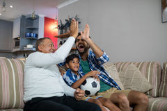 Happy family doing high five while watching soccer match Royalty Free Stock Images