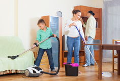 Happy family doing housework together. Happy family of three doing housework together Royalty Free Stock Photos
