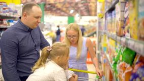 Happy family doing shopping. Family walking through the supermarket. Family makes purchases in the supermarket. Family
