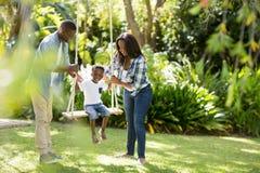 Happy family doing swing Stock Photos