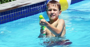 Happy family doing water gun battle in swimming pool stock video footage