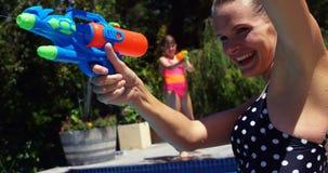 Happy family doing water gun battle in swimming pool stock video