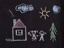 Happy family drawing with chalk. Children. Children`s drawing with crayons. Happy family near the house around the beautiful nature Stock Photo