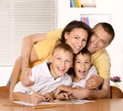 Happy family drawing. With colorful pencils at the table together Stock Images