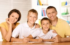 Happy family drawing with pencils. Happy family drawing with colorful pencils at the table together Stock Photos