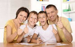 Happy family drawing at the table together. And showing thumb up Stock Photography