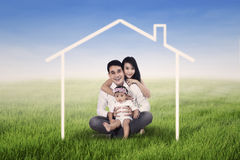Happy family dreaming a home. Happy family seated on the grass field and surrounded by home drawing Royalty Free Stock Photo