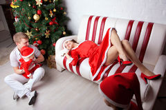 Happy family dressed in Santa costumes at home. Stock Photos