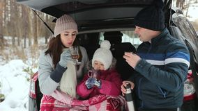 Happy family drink tea and enjoy the winter landscape. Family holiday in the winter forest. stock video
