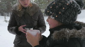 Happy family drinking hot tea outside in winter 96fps stock footage