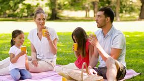 Happy family drinking juice on picnic at park stock video