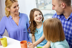 Happy family drinking tea with cups at home Royalty Free Stock Photo