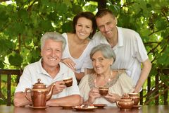 Family drinking tea outdoors. Happy family drinking tea at table outdoors in summer time Royalty Free Stock Photo