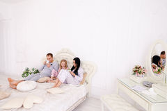 Happy family drinks tea or coffee in pajamas smiling and looking Royalty Free Stock Photography